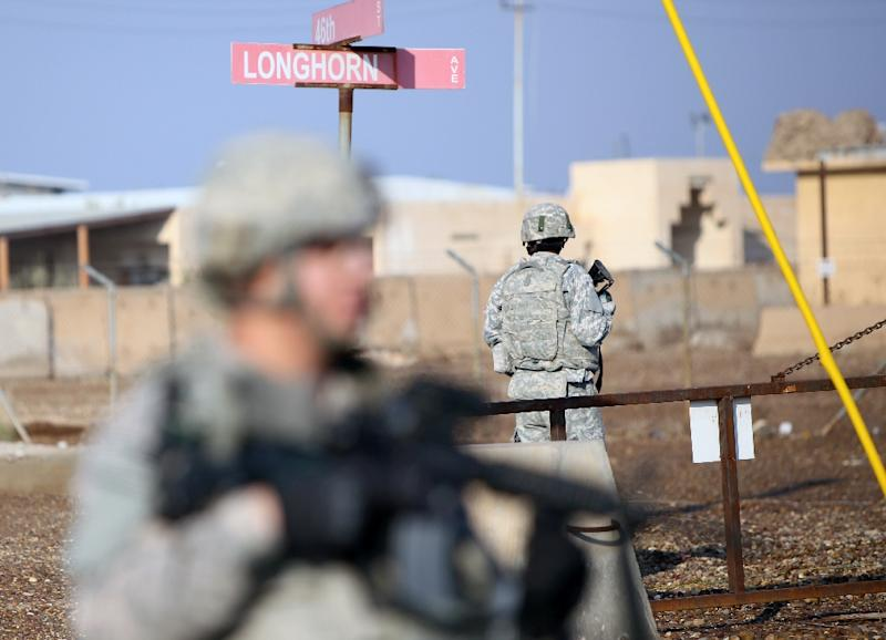 US soldiers stand guard at the Taji base complex which hosts Iraqi and US troops and is located thirty kilometres north of the capital Baghdad on December 29, 2014