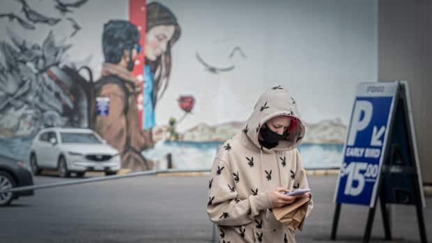 A pedestrian checks their phone while walking along Bank Street near Gladstone Avenue in late April 2021. (Brian Morris/CBC - image credit)