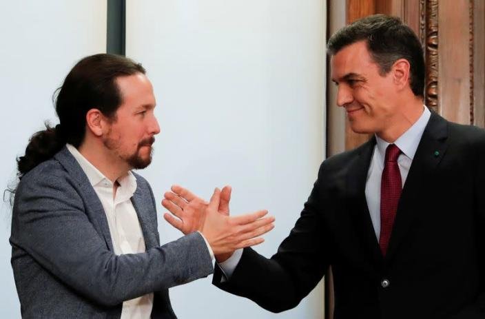 FILE PHOTO: Spain's acting PM Sanchez and Unidas Podemos leader Iglesias present their coalition agreement in Madrid