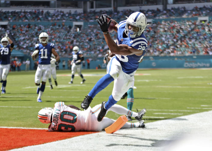 Indianapolis Colts running back Jonathan Taylor (28) runs for a touchdown against Miami Dolphins strong safety Jason McCourty (30) during the second quarter of an NFL football game Sunday, Oct. 3, 2021, in Miami Gardens, Fla. (David Santiago/Miami Herald via AP)