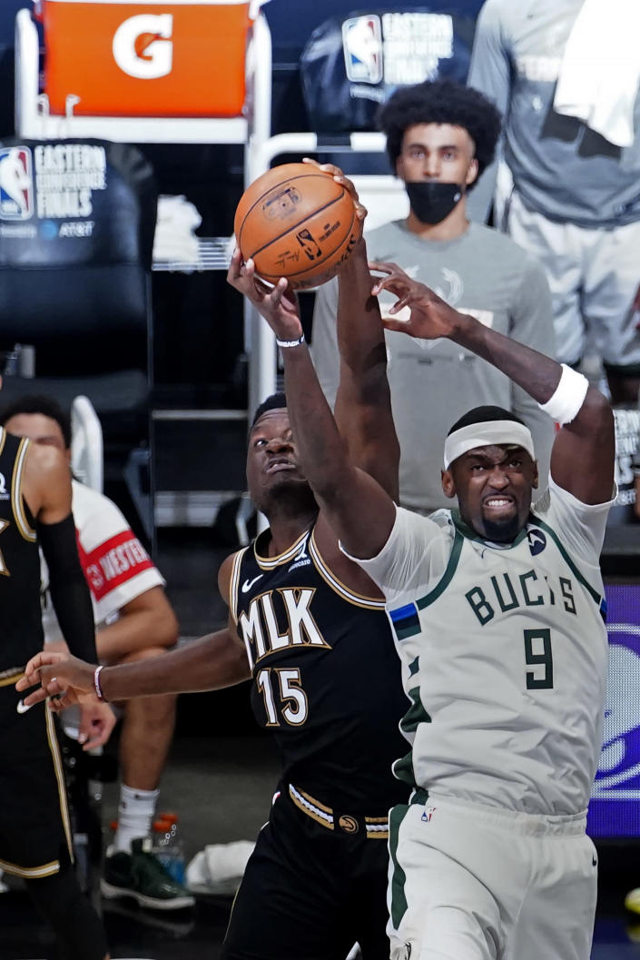 Milwaukee Bucks center Bobby Portis (9) and Atlanta Hawks center Clint Capela (15) reach for a rebound during the first half in Game 6 of the Eastern Conference finals in the NBA basketball playoffs Saturday, July 3, 2021, in Atlanta. (AP Photo/John Bazemore)