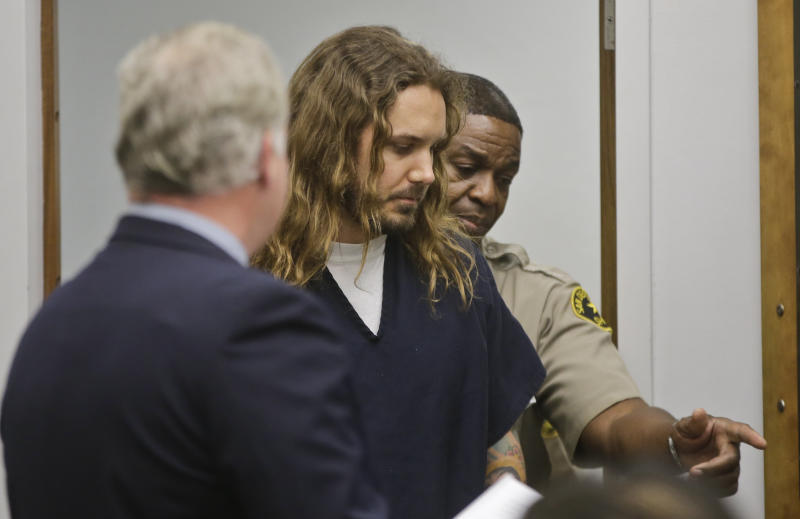 Tim Lambesis, the lead singer for the Metal band As I Lay Dying, is escorted by a San Diego sheriff deputy into Superior Court for his arraignment on charges he allegedly attempted to hire a hit man to kill his wife in Vista, Calif., Thursday, May 9, 2013. Lambesis was charged late Wednesday with one felony count of solicitation of murder, San Diego County district attorney spokeswoman Tanya Sierra said. (AP Photo/Lenny Ignelzi, Pool)