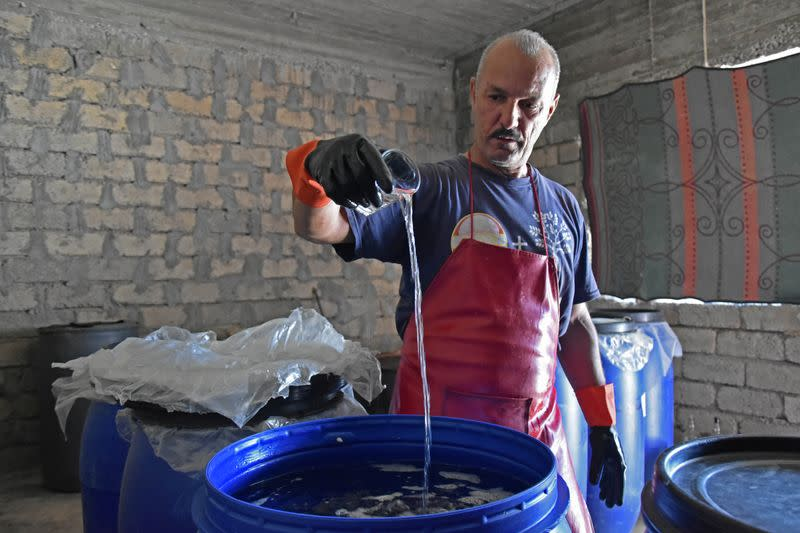 Saad Hussein, an Iraqi Yazidi, pours Arak into a fermentation tank to produce on the outskirts of Mosul