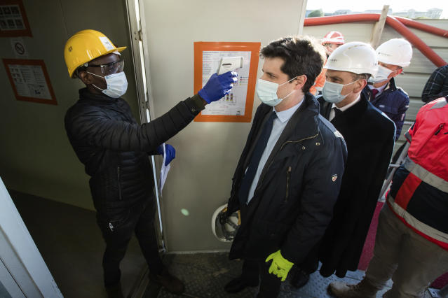 French Junior Minister for Cities and Housing Julien Denormandie has his temperature checked as he visit a construction site, following the return of economic activity and the organization of security measures in Montevrain, near Paris, Tuesday, May 12 2020. Clothing stores, coiffures and other businesses large and small were reopening on Monday with strict precautions to keep the coronavirus at bay. (Christophe Petit Tesson, Pool via AP)