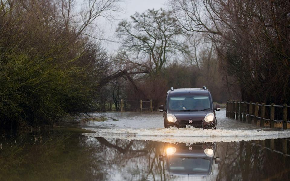 A car makes its way along a flooded road in Mountsorrel, Leicestershire on Friday - Joe Giddens/PA
