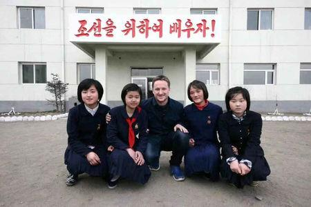 """Canadian businessman Michael Spavor poses with girls at a school in Rason Special Economic Zone, North Korea, 2012. The Korean characters behind read """"Let's study for Korea!""""  REUTERS/James Pearson"""
