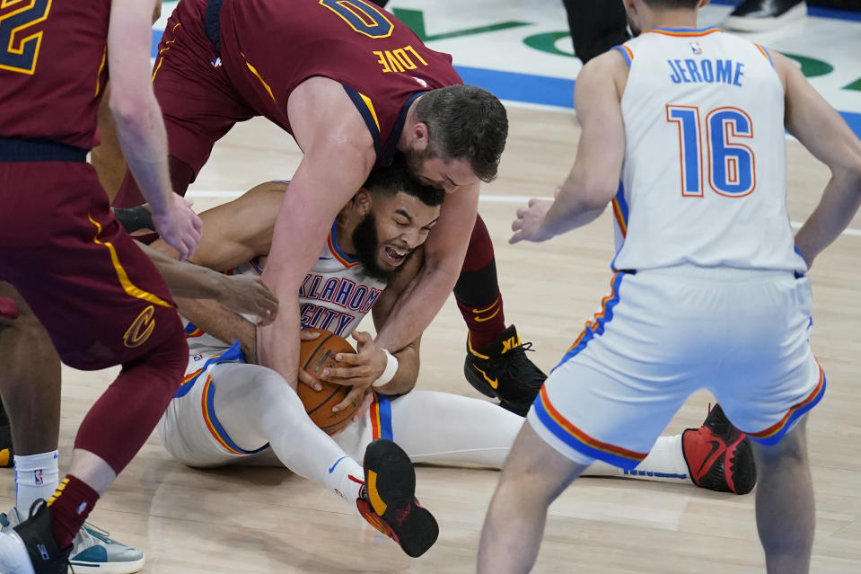 Cleveland Cavaliers forward Kevin Love, top, and Oklahoma City Thunder forward Kenrich Williams try to get control of the ball during the second half of an NBA basketball game Thursday, April 8, 2021, in Oklahoma City. (AP Photo/Sue Ogrocki)