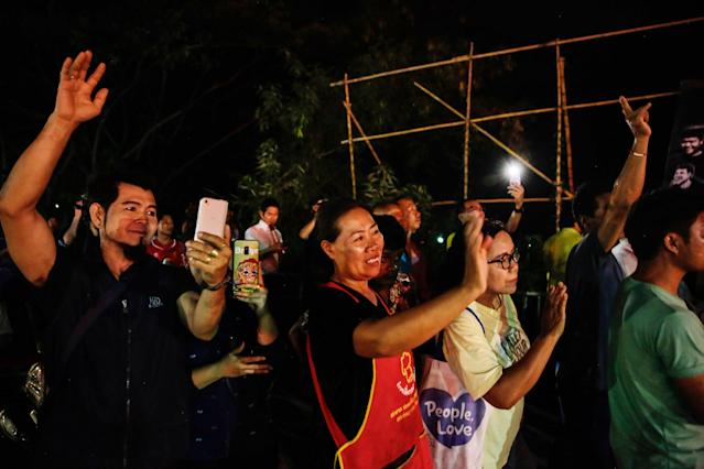 <p>Onlookers cheer as ambulances transport rescued schoolboys from a helipad to a hospital on July 9, 2018, in Chiang Rai, Thailand. Videos released by Thai navy SEALs showed the boys, aged 11 to 16, and their 25-year-old coach are in good health. (Photo: Lauren DeCicca/Getty Images) </p>