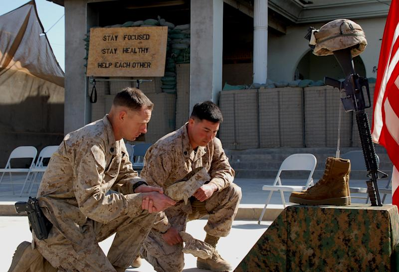 In this Feb. 24, 2011 photo, U.S. Marine Staff Sgt. Nathan Stocking, 27, from Phoenix, left, and U.S. Marine Staff Sgt. Todd Voeller, 28, from Glendale, Ariz., right, pay tribute to a Marine killed in action from 2nd Platoon, Lima Company, 3rd Battalion, 5th Marine Regiment during a memorial ceremony in Sangin district southern Helmand province of Afghanistan. When U.S. Marine Lance Cpl. Derek Goins deployed to the most dangerous place in Afghanistan five months ago, he mentally prepared for the risk of getting shot by the Taliban and stepping on homemade bombs buried throughout this southern river valley. (AP Photo/Sebastian Abbot)