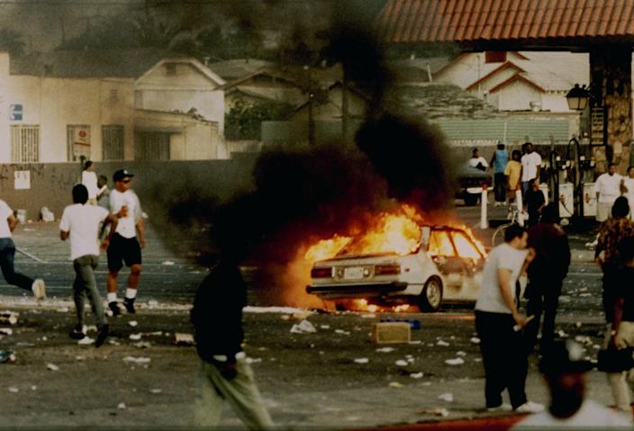 A car burns as looters take to the streets at the intersection of Florence and Normandie Avenues in Los Angeles on April 29, 1992.