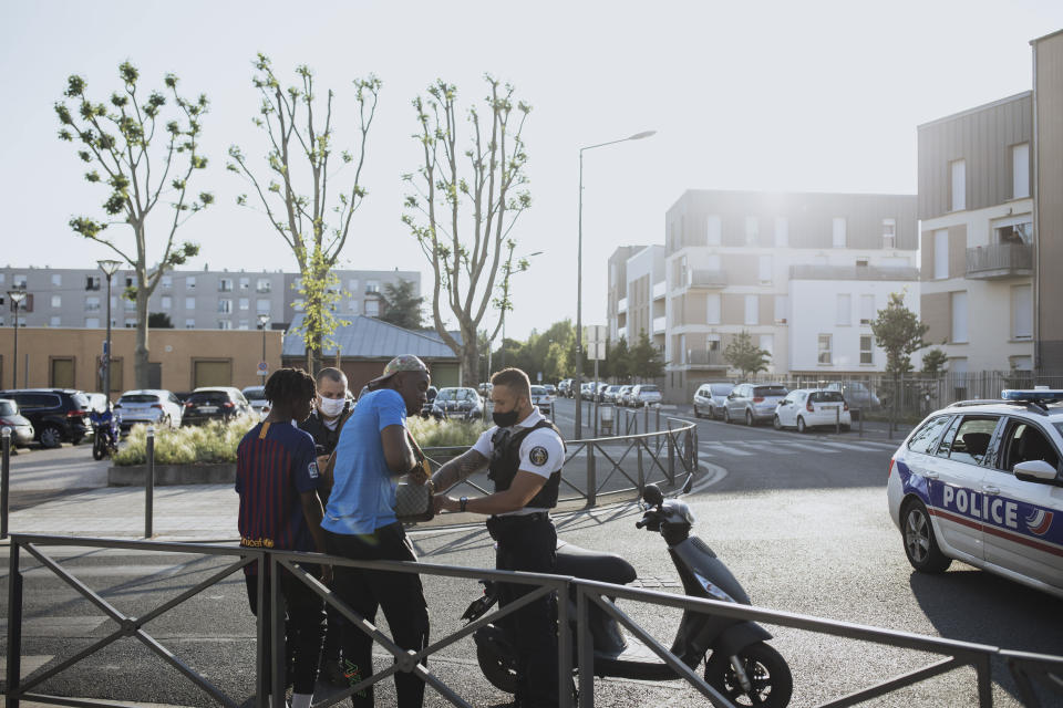 Police officers stop and search a motorbike driver and his passenger who did not wear any helmets, in the Paris suburb of Villiers-le-Bel on Tuesday, June, 15, 2021. (AP Photo/Lewis Joly)
