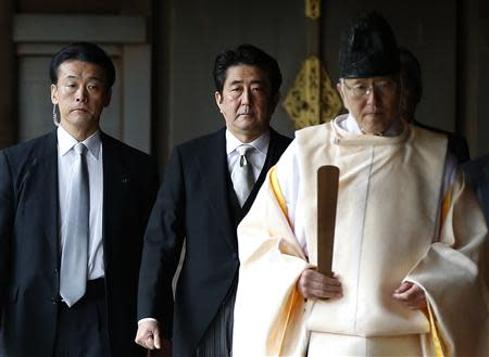 Japan's Prime Minister Shinzo Abe (C) is led by a Shinto priest as he visits Yasukuni shrine in Tokyo in this December 26, 2013 file photo. REUTERS/Toru Hanai