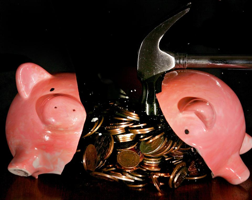 A traditional piggy bank is smashed open with a hammer. Photo: Anthony Devlin /PA