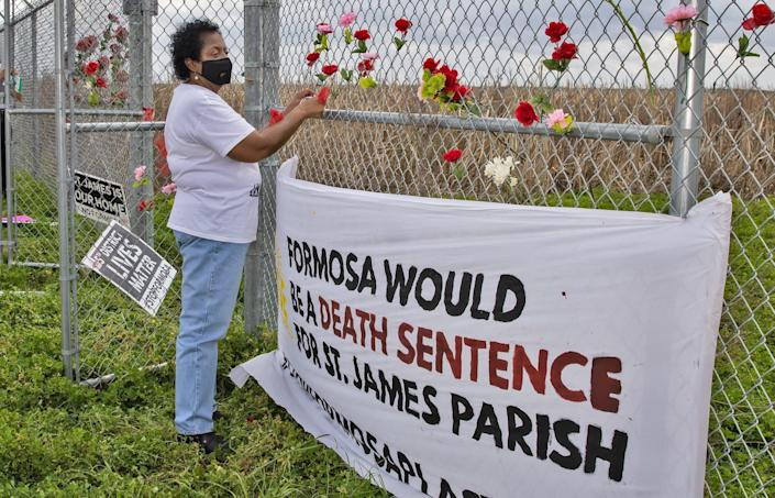 sharon lavigne looks out beyond a fence, next to a sign that reads 'formosa would be a death sentence for st. james parish'