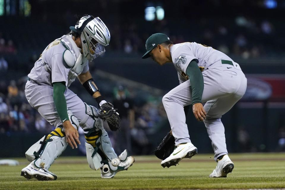 Oakland Athletics starting pitcher Jesus Luzardo, right, and Athletics catcher Aramis Garcia, left, are unable to make a play on a bunt single by Arizona Diamondbacks' Zac Gallen during the second inning of a baseball game Tuesday, April 13, 2021, in Phoenix. (AP Photo/Ross D. Franklin)