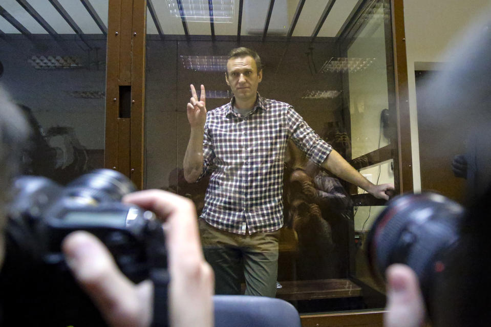 Russian opposition leader Alexei Navalny gestures posing for photographers as he stands in a cage in the Babuskinsky District Court in Moscow, Russia, Saturday, Feb. 20, 2021. A Moscow court has rejected Russian opposition leader Alexei Navalny's appeal against his prison sentence. Earlier this month, a lower court sentenced Navalny to two years and eight months in prison for violating terms of his probation while recuperating in Germany from a nerve agent poisoning that he blames on the Kremlin. (AP Photo/Alexander Zemlianichenko)