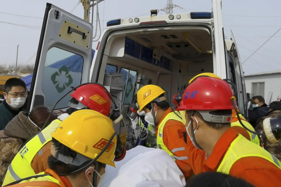In this photo released by Xinhua News Agency, rescuers carry a miner who was trapped in a gold mine in Qixia City in east China's Shandong Province, Sunday, Jan. 24, 2021. Rescuers in China on Sunday lifted several trapped miners to the surface who were trapped for two weeks after an explosion in a northern gold mine, state media reported. (Luan Qincheng/Xinhua via AP)
