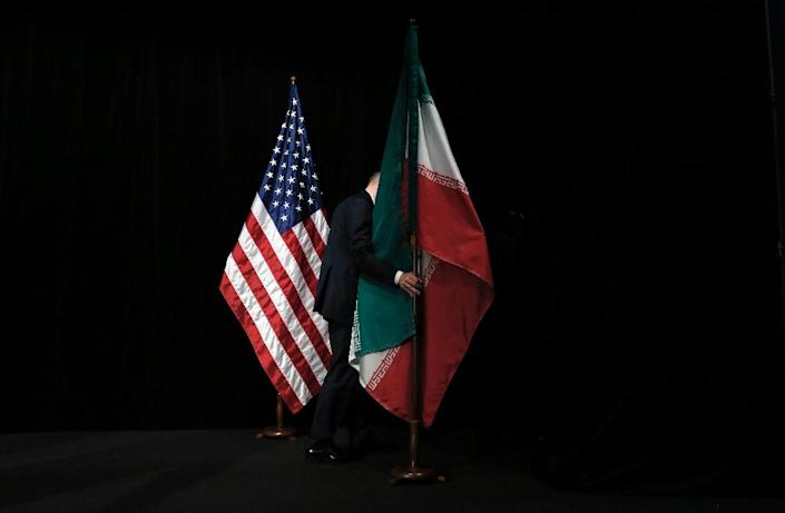 A staffer removes the Iranian flag from the stage after a group picture with foreign ministers and representatives of the United States, Iran, other nations and the European Union on July 14, 2015, when the Iran nuclear deal was signed (AFP Photo/CARLOS BARRIA)