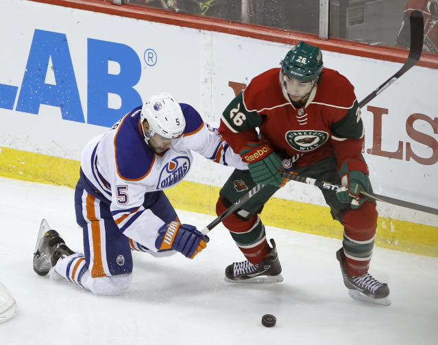 Edmonton Oilers defenseman Mark Fraser (5) and Minnesota Wild left wing Matt Moulson (26) tangle as they chase the puck during the first period of an NHL hockey game in St. Paul, Minn., Tuesday, March 11, 2014. (AP Photo/Ann Heisenfelt)