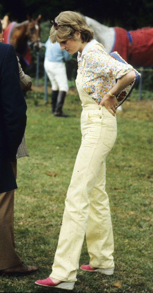<p>In a Liberty-print shirt, yellow dungarees, and pink espadrilles at a polo match in England. </p>