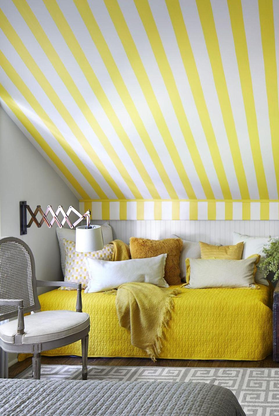 <p>Here's proof that you can be bold and bright while still maintaining a clean, sophisticated aesthetic. The yellow stripes on the ceiling make the whole room pop, while the grays mellow things out just a touch. We also love the idea of putting a bed in the corner, where it feels more private and cozy. </p>