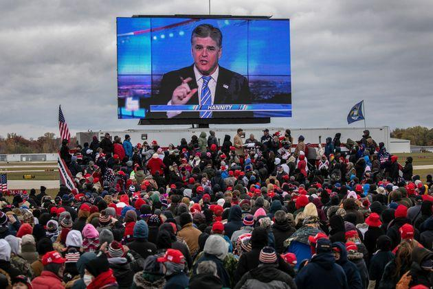 Trump supporters watch Sean Hannity speak ahead of Trump's arrival at a campaign rally in Waterford, Michigan, last year. (Photo: John Moore via Getty Images)