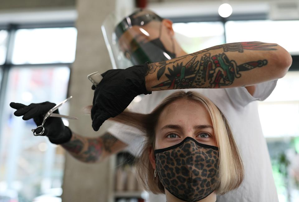 Pont Smith, co-owner and stylist of bebop hair salon in London, wears PPE as he cuts the hair of model Daisy George, during final preparations ahead of the salon's reopening, as further coronavirus lockdown restrictions are lifted in England. (Photo by Yui Mok/PA Images via Getty Images)