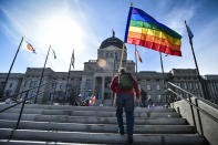 FILE - In this March 15, 2021, file photo, demonstrators gather on the steps of the Montana State Capitol protesting anti-LGBTQ+ legislation in Helena, Mont. Gov. Greg Gianforte signed a bill Friday, May 7, 2021, banning transgender athletes from participating in school and university sports according to the gender with which they identify, making Montana one of several Republican-controlled states to approve such measures in 2021. (Thom Bridge/Independent Record via AP, File)=MTHEL
