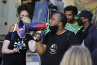 """Mark Henry Jr., center, a Black Lives Matter leader, speaks into a megaphone in a doorway of the Seattle Police Department East Precinct building, which has been boarded up and abandoned except for a few officers inside, Thursday, June 11, 2020, in Seattle. The building is located in what is being called the """"Capitol Hill Autonomous Zone."""" Following days of violent confrontations with protesters, police have largely withdrawn from the neighborhood. (AP Photo/Ted S. Warren)"""