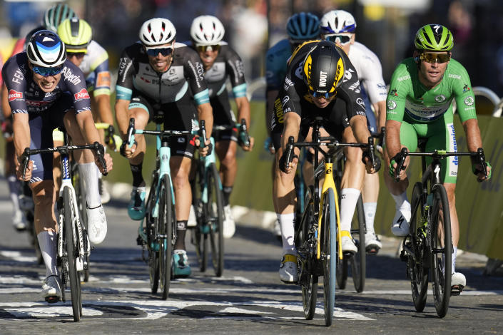 Belgium's Wout Van Aert, second left, crosses the finish line to win ahead of Britain's Mark Cavendish, wearing the best sprinter's green jersey, right, and Belgium's Jasper Philipsen, left, during the twenty-first and last stage of the Tour de France cycling race over 108.4 kilometers (67.4 miles) with start in Chatou and finish on the Champs Elysees in Paris, France,Sunday, July 18, 2021. (AP Photo/Christophe Ena)
