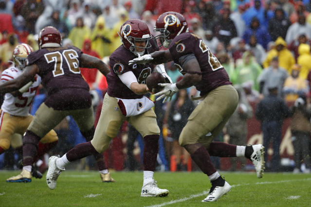 Washington Redskins quarterback Case Keenum, center, hands off the ball to Washington Redskins running back Adrian Peterson in the first half of an NFL football game against the San Francisco 49ers, Sunday, Oct. 20, 2019, in Landover, Md. (AP Photo/Alex Brandon)