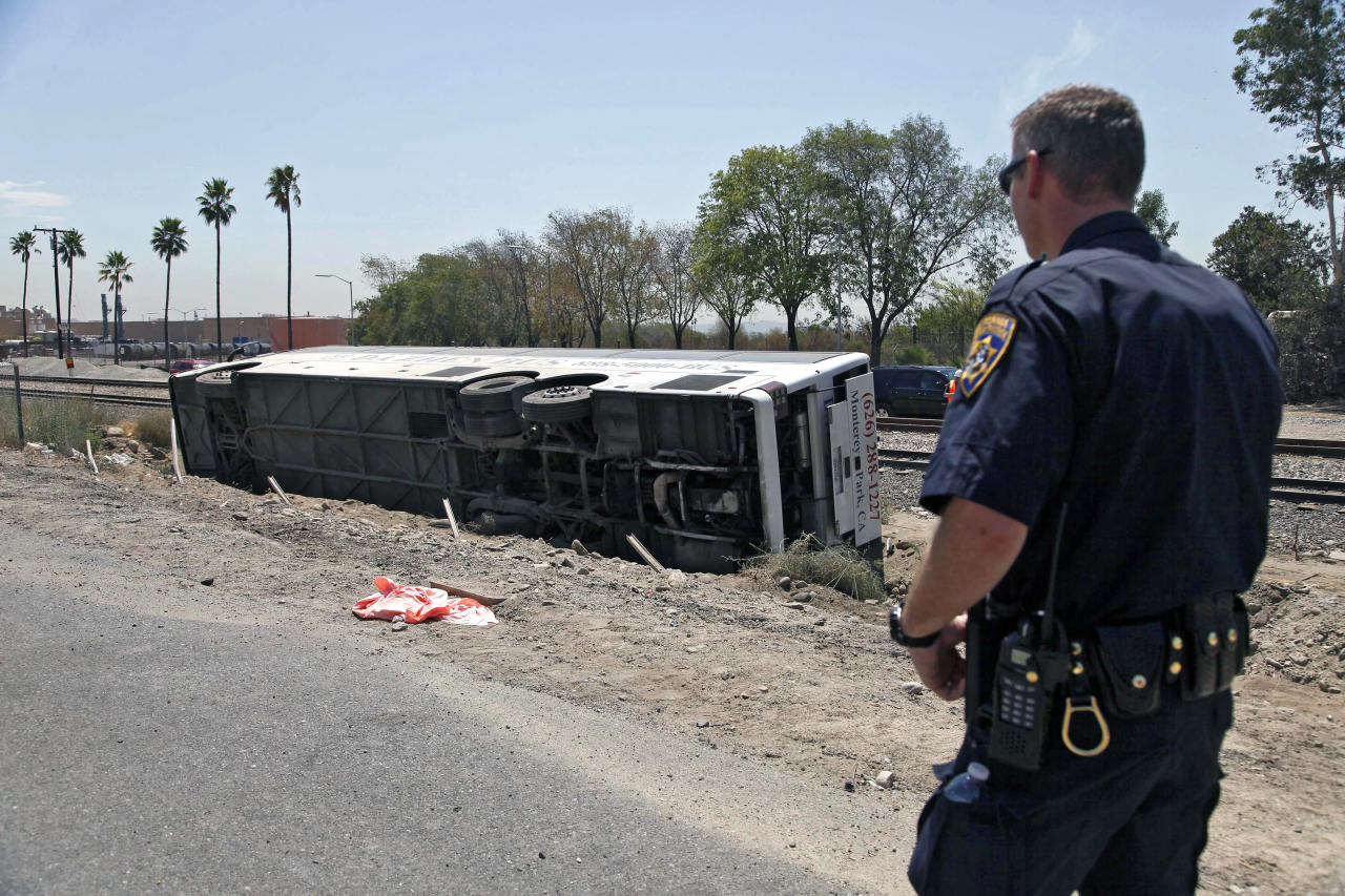A highway patrol officer looks at a bus that crashed along the side of Interstate 210 in Irwindale, Calif. on Thursday, Aug 22, 2013. The bus carrying gamblers to a casino overturned on the Southern California freeway injuring more than 50 people on board. The bus went through a chain-link fence off the side of the road and ended up on its side down a dirt embankment between the freeway and railroad tracks. (AP Photo/Nick Ut)