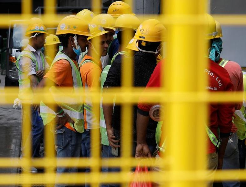 Construction workers gather around a tap to wash their hands as they break for lunch in Singapore