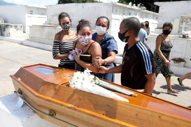 Relatives of Luiz Alves, 63, who died from COVID-19, react at his funeral in Rio de Janeiro, Brazil, on March 10, 2021. This week, Brazil set a new daily record with more than 4,000 deaths.  (Pilar Olivares/Reuters - image credit)