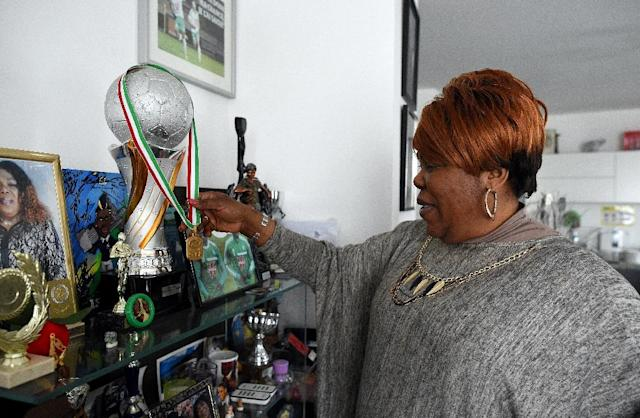 Yeo Moriba, the mother of footballer Paul Pogba, poses in with medals, trophies and photos on March 16, 2016 in Bussy Saint Georges, east of Paris (AFP Photo/Franck Fife)