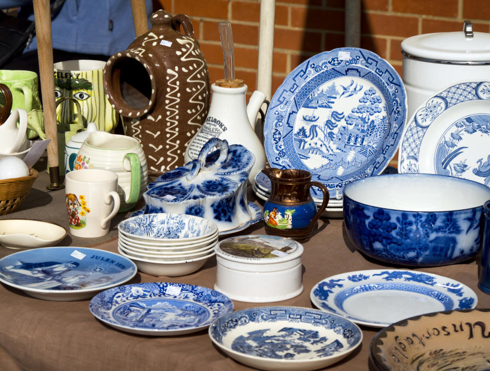 Fakenham, Norfolk, England - September 24, 2015: A market stall selling old china. There is a variety of ages, types and styles including plates, jugs, mugs, dishes, bowls and an inhaler, seen on a bright and sunny early autumn day.