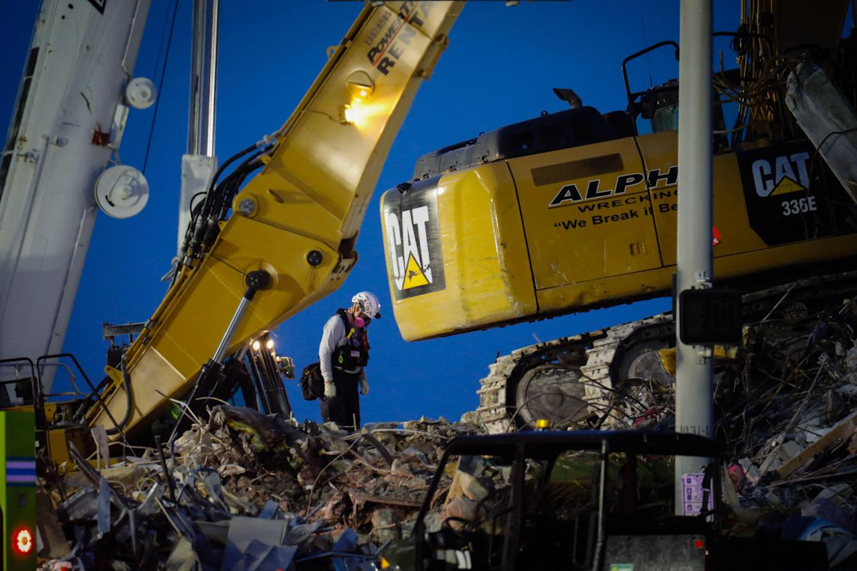 A worker searches in the rubble at the site of the collapsed Champlain Towers South condo in Surfside, Fla., Tuesday. (Photo by Eva Marie Uzcategui/AFP via Getty Images)