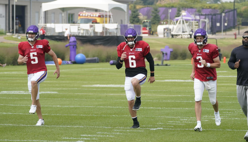Minnesota Vikings quarterbacks Jake Browning, right, and Danny Etling (6) and Case Cookus take part in calisthenics during an NFL football training camp at TCO Stadium, Tuesday, Aug. 3, 2021, in Eagan, Minn. (AP Photo/Jim Mone)