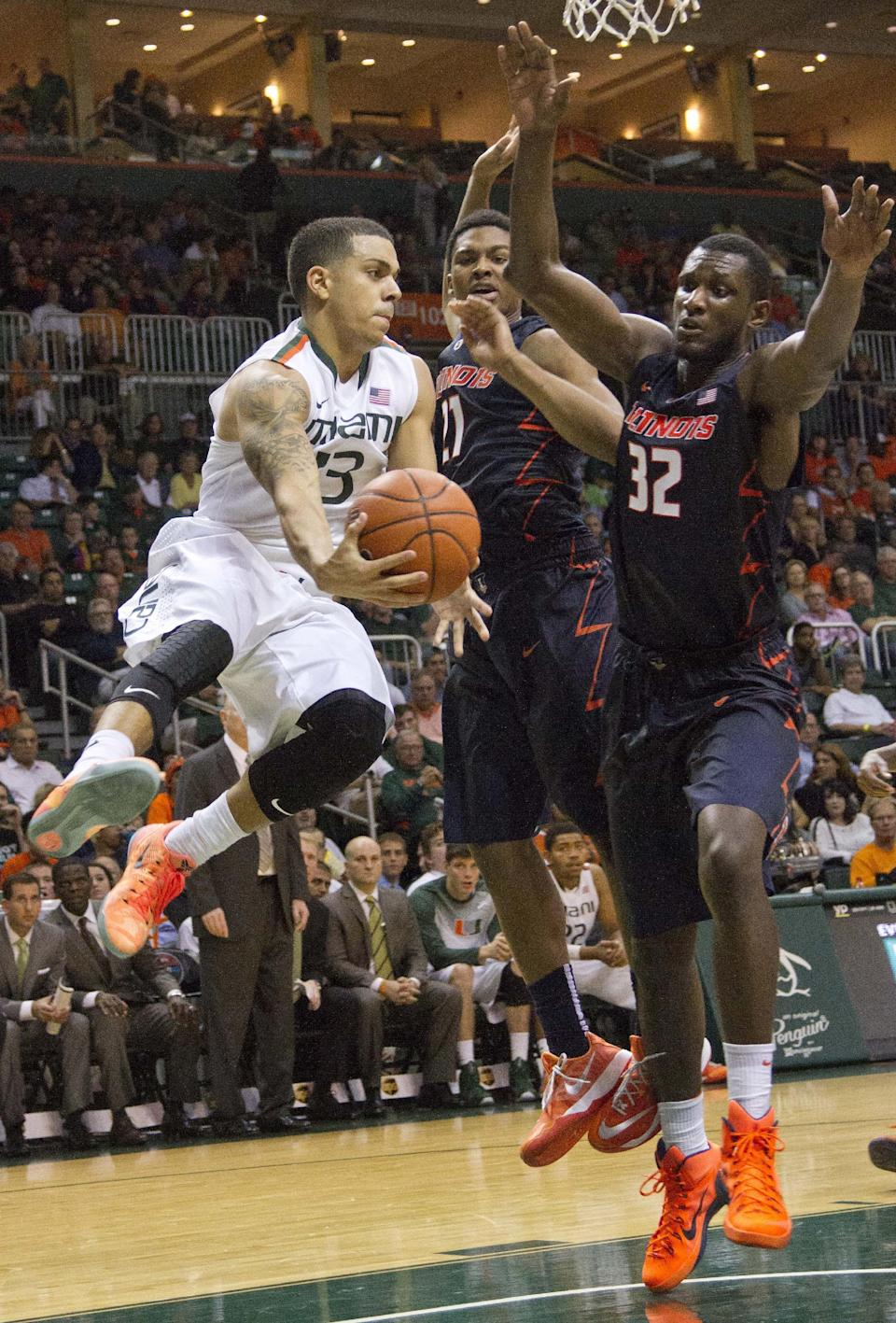 Miami guard Angel Rodriguez, left, passes the ball past Illinois guard Malcolm Hill, center, and forward/center Nnanna Egwu (32) during the second half of an NCAA college basketball game, Tuesday, Dec. 2, 2014 in Coral Gables, Fla. Miami defeated Illinois 70-61. (AP Photo/Wilfredo Lee)