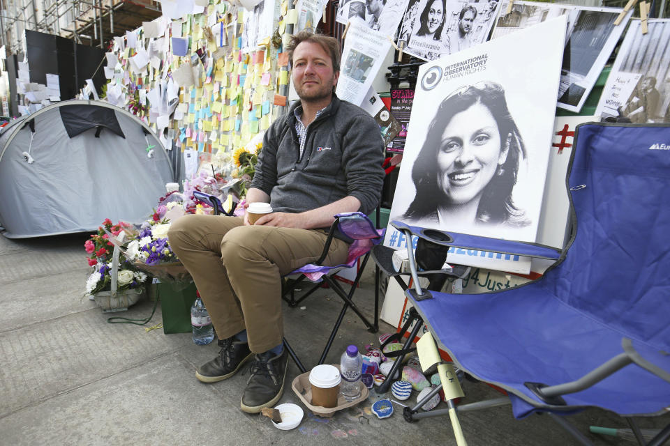 Richard Ratcliffe, the husband of detained Nazanin Zaghari Ratcliffe, seen in poster, outside the Iranian Embassy in London, Saturday June 29, 2019, on the day he ended his 15-day hunger strike and his imprisoned wife also ended her own hunger in an Iran jail.  Richard Ratcliffe has been camping outside the Iranian Embassing to support his wife Nazanin Zaghari-Ratcliffe, the British-Iranian woman convicted in 2016 and jailed for five years for alleged spying against Iran. (Jonathan Brady/PA via AP)