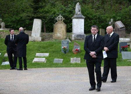 Private security guards stand outside Highgate Cemetery in London