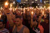 <p>People hold candles during an evening memorial service for the victims of the Pulse Nightclub shootings, at the Dr. Phillips Center for the Performing Arts in Orlando, Florida.</p>