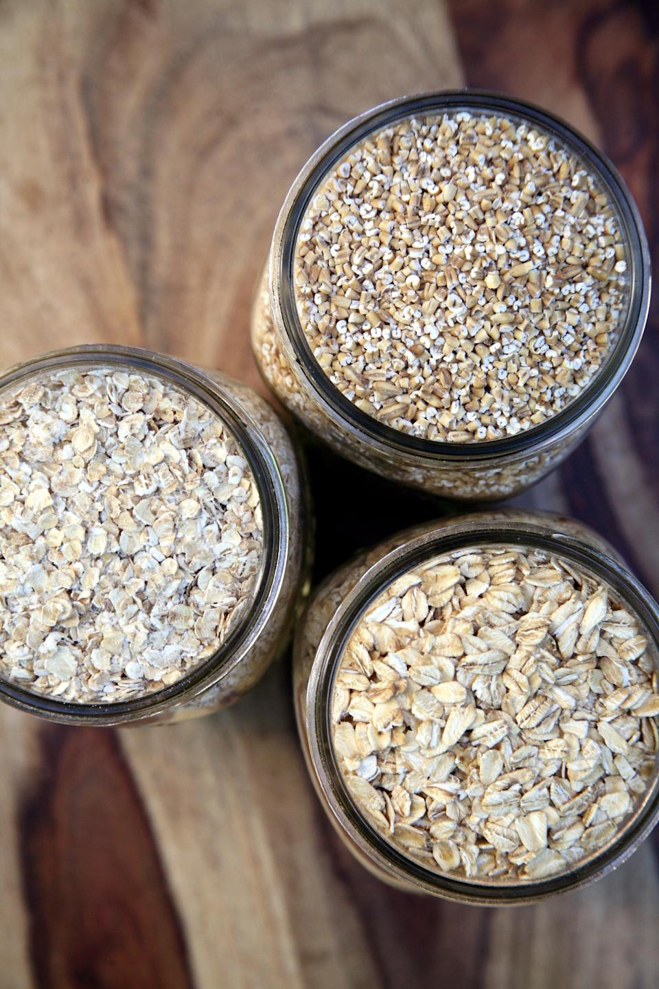 """<p>One of the best reasons to eat oatmeal is because it's high in fiber. Freeman said this whole grain has both soluble and insoluble fiber, which are both """"beneficial for promoting satiety, regular bowel movements, and controlling blood glucose levels."""" The soluble fiber in oatmeal can also help raise your HDL (good) levels of cholesterol and <a href=""""https://www.ncbi.nlm.nih.gov/pmc/articles/PMC5885279/"""" class=""""link rapid-noclick-resp"""" rel=""""nofollow noopener"""" target=""""_blank"""" data-ylk=""""slk:lower your LDL (bad) cholesterol levels"""">lower your LDL (bad) cholesterol levels</a> by reducing the absorption of cholesterol into your bloodstream. Also, oats have a lower glycemic index than potatoes or white bread, another way it can help to stabilize blood-sugar levels.</p> <p>There are <a href=""""https://www.popsugar.com/fitness/Comparison-Steel-Cut-Oats-Old-Fashioned-Oats-Quick-Oats-5321167"""" class=""""link rapid-noclick-resp"""" rel=""""nofollow noopener"""" target=""""_blank"""" data-ylk=""""slk:various forms of oatmeal"""">various forms of oatmeal</a>, and similar to other types of whole grains, the less processed, the more beneficial, Freeman explained. See the ranking below, from least processed to more processed. As you can see, oat groats are highest in fiber.</p> <ol> <li><strong>Oat groats:</strong> The complete oat kernel is kept intact with endosperm and germ. The texture is hearty and chewy and very similar to cooked brown rice.<br> <a href=""""https://www.bobsredmill.com/organic-whole-oat-groats.html"""" class=""""link rapid-noclick-resp"""" rel=""""nofollow noopener"""" target=""""_blank"""" data-ylk=""""slk:1/4 cup uncooked"""">1/4 cup uncooked</a>: 180 calories, 34 grams carbs, five grams fiber, five grams protein</li> <li><strong>Steel-cut oats:</strong> The husk has been removed, and the kernel has been cut into smaller pieces. They have a thick, chewy texture.<br> <a href=""""https://www.bobsredmill.com/organic-steel-cut-oats.html"""" class=""""link rapid-noclick-resp"""" rel=""""nofollow noopener"""" target=""""_blank"""" data-ylk="""""""