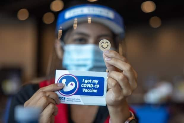 A staff member shows a vaccination sticker at a walk-in vaccination clinic at the Halifax Convention Centre. (Robert Short/CBC - image credit)