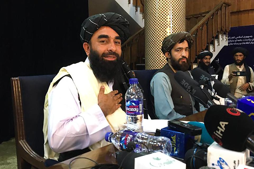 Taliban spokesperson Zabihullah Mujahid (L) attends the first press conference in Kabul on August 17, 2021, following their stunning takeover of Afghanistan. (Photo by Hoshang HASHIMI / AFP) (Photo by HOSHANG HASHIMI/AFP via Getty Images)