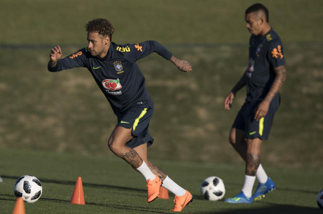 Brazil's Neymar, left, runs with the ball during a practice session of the Brazil national soccer team at the Granja Comary training center, in Teresopolis, Brazil, Tuesday, May 22, 2018. (AP Photo/Leo Correa)