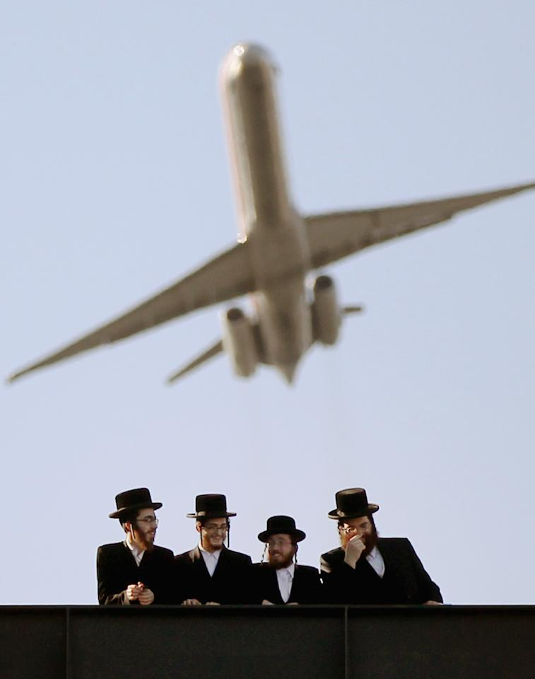 Ultra-Orthodox Jews gather at Citi Field as a plane takes off overhead from LaGuradia Airport at a meeting to discuss the risks of using the Internet on May 20, 2012 in the Queens borough of New York City. More than 40,000 were expected to attend the rally at Citi Field, the home of the New York Mets, which organizers said would promote religiously responsible ways to use the Internet.  (Photo by Mario Tama/Getty Images)