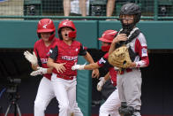 Hamilton, Ohio's JJ Vogel, left, Gage Maggard, left center, and Hamilton, Ohio's Krew Brown, right center, celebrate behind Sioux Falls, S.D. catcher Easton Riley after scoring during the second inning of a baseball game at the Little League World Series in South Williamsport, Pa., Saturday, Aug. 28, 2021. (AP Photo/Gene J. Puskar)