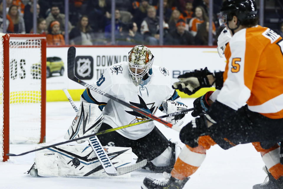 San Jose Sharks' Aaron Dell (30) blocks a shot by Philadelphia Flyers' Philippe Myers (5) during the second period of an NHL hockey game, Tuesday, Feb. 25, 2020, in Philadelphia. (AP Photo/Matt Slocum)