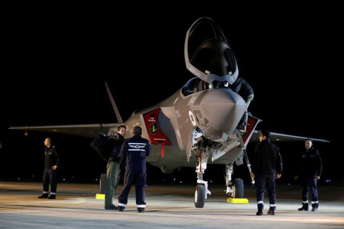 FILE PHOTO: Israeli soldiers walk near a F-35 fighter jet after it landed in Israel at Nevatim air base after the Israeli air force bought them at Nevatim